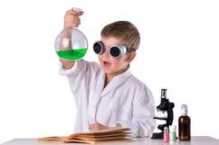 黑玻璃的科学家男孩拿着有绿色流体的一个烧瓶在他的手上 免版税库存照片