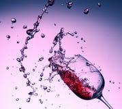 从玻璃的红葡萄酒飞溅在紫色背景 免版税库存照片