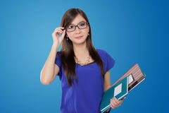 玻璃的美丽的年轻亚裔老师,在蓝色背景 库存图片