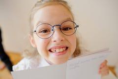 玻璃的逗人喜爱的矮小的女小学生显示她的习字簿 免版税图库摄影