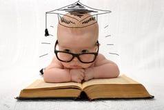 玻璃的逗人喜爱的矮小的婴孩与被绘的教授帽子 免版税库存图片