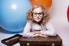 玻璃的青少年的女孩与在家神背景的木算盘  免版税库存图片