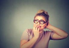 玻璃的紧张的被注重的年轻讨厌的妇女咬住指甲盖的急切地看 库存照片