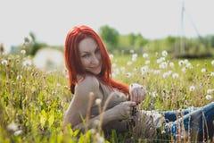 玻璃的年轻时兴的可爱的性感的女孩坐延命菊草甸晴朗的夏日 免版税库存照片