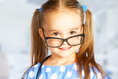 玻璃的滑稽的微笑的儿童女孩 免版税库存图片
