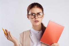 玻璃的年轻美丽的妇女在白色隔绝了背景拿着笔记本,老师,画象 库存照片