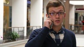 玻璃的年轻英俊的人谈话在商城的手机 特写镜头 股票录像