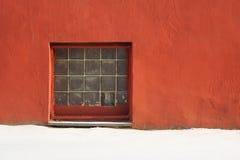 玻璃砖在红色的正方形窗口涂了灰泥有copyspace的墙壁 免版税库存照片