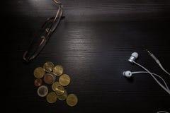 玻璃硬币耳机书桌办公室工作区反对黑对比细节 库存照片