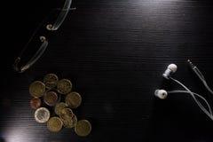 玻璃硬币耳机书桌办公室工作区反对黑对比细节 免版税库存图片