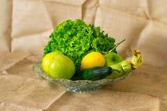 玻璃碗用新鲜的蔬菜沙拉、柠檬、苹果、绿皮胡瓜和黄瓜 免版税库存图片