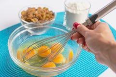玻璃碗用鸡蛋和女性手与扫,套  免版税库存图片