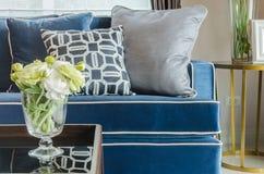 玻璃花瓶在桌上的花在有蓝色经典之作的s客厅 免版税库存照片