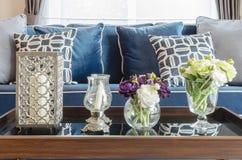 玻璃花瓶在桌上的花在有蓝色经典之作的s客厅 免版税库存图片