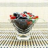 玻璃花瓶用黑和红浆果 图库摄影