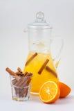玻璃蒸馏瓶用橙汁、桂香和冰 免版税库存图片