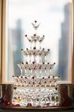 玻璃金字塔用香槟和樱桃 玫瑰 免版税库存图片