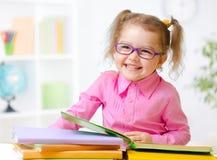 玻璃阅读书的愉快的儿童女孩在屋子里 免版税库存图片