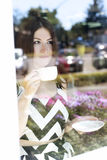 玻璃陈列室的年轻美丽的女孩咖啡馆,晴天,拿着杯子茶 免版税图库摄影