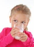 玻璃饮用的女孩少许牛奶 库存照片