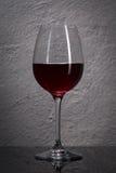 玻璃 在石花岗岩墙壁前面的红葡萄酒玻璃 库存图片