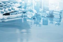 玻璃医学小瓶一次用量的针剂、医学药片和胶囊注射器在X光片在医生桌背景的与拷贝 库存照片
