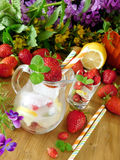 玻璃水罐冰块、莓果、柠檬和薄菏有很多 免版税库存照片