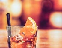玻璃细节喷开胃酒与橙色切片和冰块的aperol鸡尾酒在酒吧桌,葡萄酒大气背景上 免版税库存图片