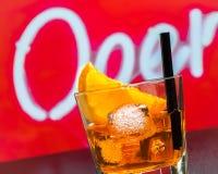 玻璃细节喷开胃酒与橙色切片和冰块的aperol鸡尾酒在酒吧桌,迪斯科大气背景上 库存图片