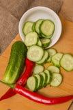 黄瓜和红辣椒在一个木木盘 免版税库存图片