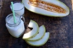 瓜圆滑的人,切片在桌上的瓜,酸奶 概念吃健康 纯素食主义,素食主义 免版税库存照片