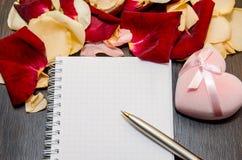 瓣上升了与礼物盒和空的卡片在桌上 在红色玫瑰色华伦泰白色的概念重点 免版税库存照片