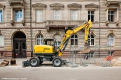 瓦克Neuson运转在城市环境里的黄色挖掘机 库存图片