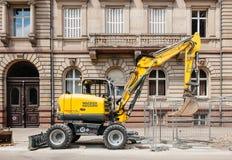 瓦克Neuson运转在城市环境里的黄色挖掘机 免版税图库摄影