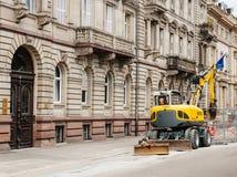 瓦克Neuson运转在城市环境里的黄色挖掘机 库存照片