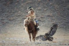 瓦剌,寻找与鹫 年轻蒙古女孩-在马背上参加鹫节日的猎人 免版税库存图片