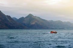 瓦卡蒂普湖,昆斯敦,新西兰的南岛,当速度喷气机小船被看见从遥远 库存照片