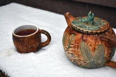 瓦器杯子通入蒸汽的红茶和在落的一个茶壶下雪 免版税库存图片