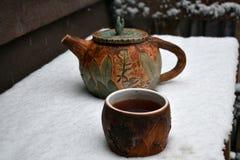 瓦器杯子通入蒸汽的红茶和在落的一个茶壶下雪 免版税库存照片