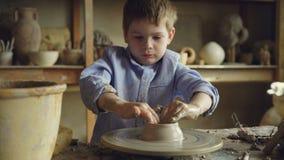 瓦器类的年轻男孩学生铸造在陶瓷工` s轮子的黏土,学会传统工艺 严肃的孩子是 股票录像