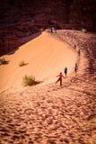 瓦地伦,约旦- 2009年11月:游人在瓦地伦联合国科教文组织世界遗产攀登橙色沙漠沙丘在约旦 免版税库存照片