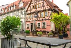瓦尔多夫,德国- 2017年6月4日:一张金属桌和一把椅子在一个咖啡馆在历史的老镇正方形  免版税库存图片