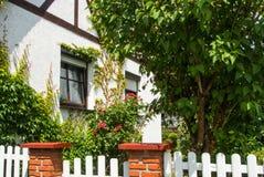 瓦尔多夫,德国- 2017年6月4日:有开花的玫瑰的一个庭院在传统德国白色房子附近 图库摄影