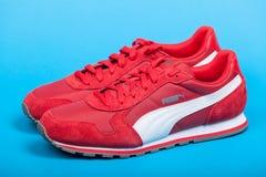 瓦尔纳,保加利亚- 2017年6月17日 在蓝色背景的红色美洲狮体育鞋子 美洲狮,一个主要德国跨国公司 产品sho 库存照片