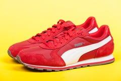 瓦尔纳,保加利亚- 2017年6月17日 在黄色背景的红色美洲狮体育鞋子 美洲狮,一个主要德国跨国公司 产品s 图库摄影