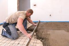 瓦工在一个最近建造的房子里排列水泥冗长的句子 库存照片