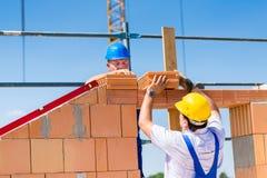 瓦工或建造者在建造场所工作 免版税库存照片