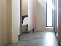 瓦片在洗手间小室,洗手间内部洗手间围住在办公室 与洗手间的被打开的门在背景中 免版税库存图片