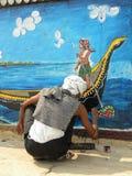 瓦腊纳西、北方邦、印度- 2009年11月2日在墙壁上的一张艺术家绘画有画笔的和颜色 库存图片