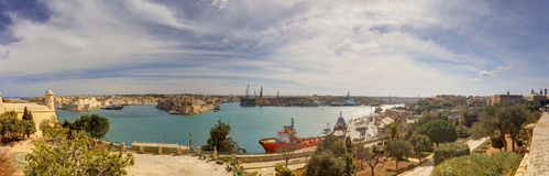 瓦莱塔市港口区域的全景视图在马耳他,有沿海岸线和一艘红色船的许多历史建筑的 免版税库存照片